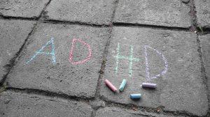 Napis ADHD zrobiony kredą na chodniku