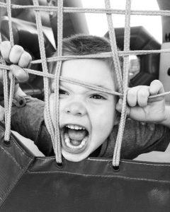 Krzyczący chłopiec patrzący przez liny