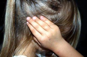Dziewczynka zasłaniająca uszy