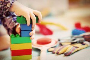 Dziecko układające kolorowe klocki