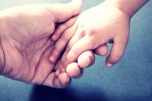Rodzic trzyma dziecko za rękę