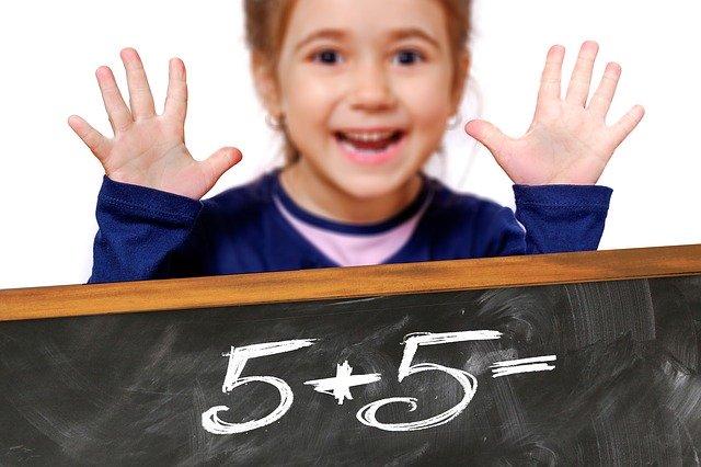 Na pierwszym planie działanie napisane na tablicy 5+5=, w tle dziewczynka pokazująca 10 paluszków