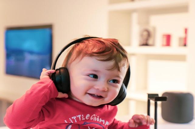 Uśmiechający się chłopiec w słuchawkach słuchający muzyki