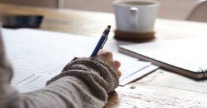 Ręka osoby, która coś zapisuje długopisem, w tle filiżanka