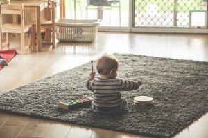 Małe dziecko siedzące na dywanie i grające na cymbałakch i bębenku