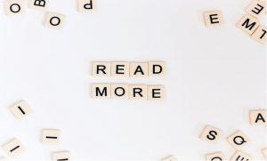 """Napis """"READ MORE"""" ułożony z kostek gry Scrabble"""