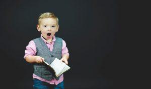 Zaskoczony chłopiec z książką